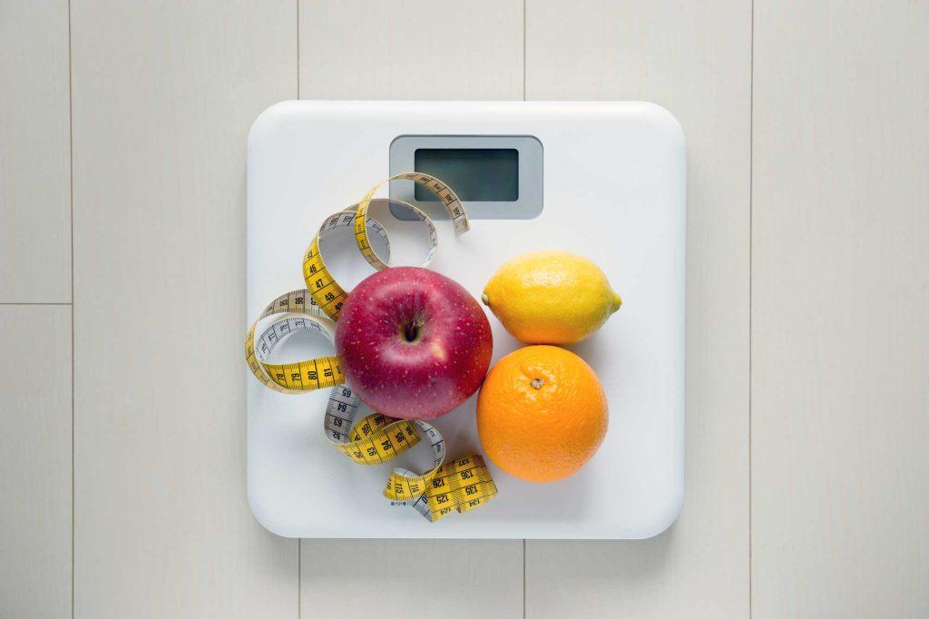 体重計の上のメジャーと果物
