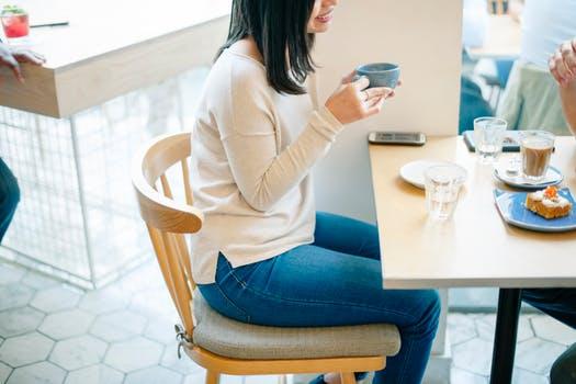 椅子に座って飲み物を飲む女性