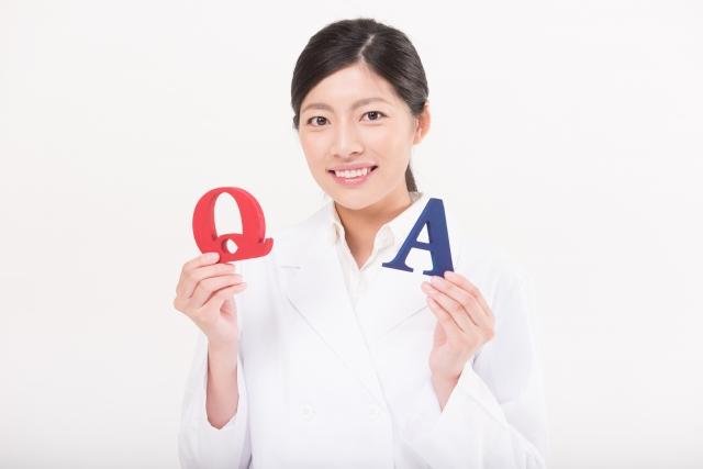 QとAの模型を持つ女性