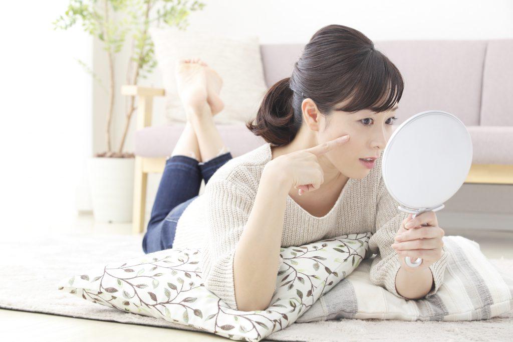 鏡を見ながら寝転ぶ女性