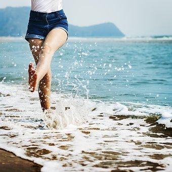 砂浜で波を蹴っている女性の画像