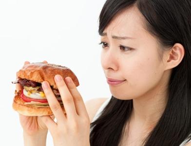 ハンバーガーを見つめる女性の画像