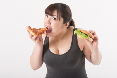 ピザとハンバーガーを食べる女性