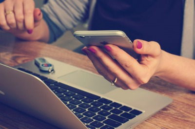 スマホとパソコンを見る女性