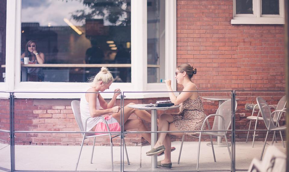 足を組んで座る女性2人