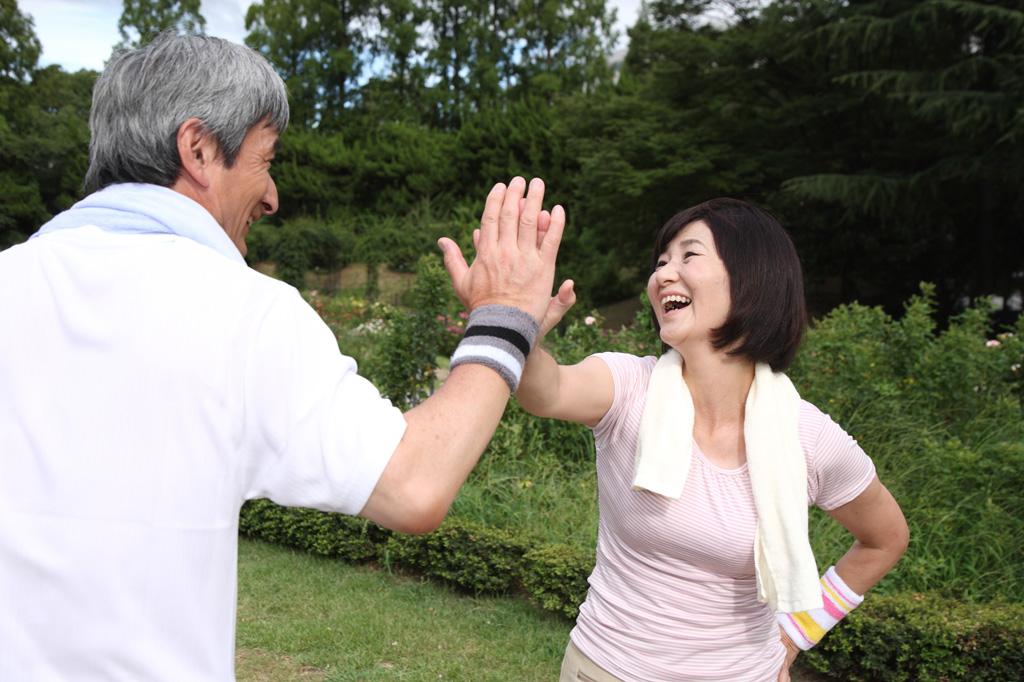 ハイタッチをする中高年の夫婦