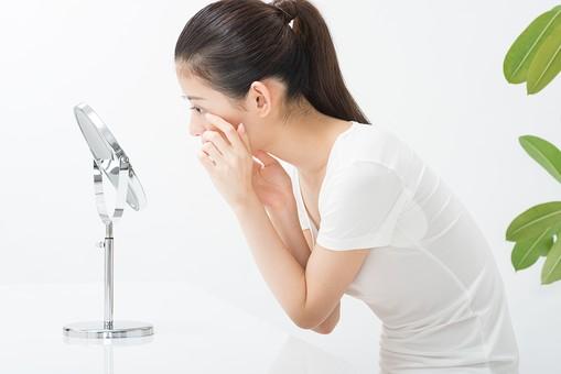 鏡で目元を確認する女性