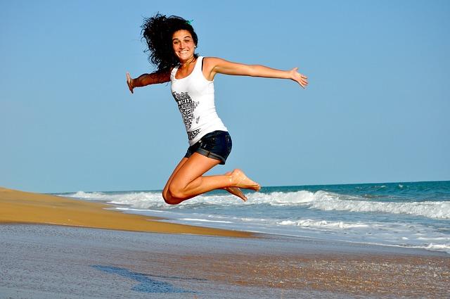 海辺で飛び跳ねる女性