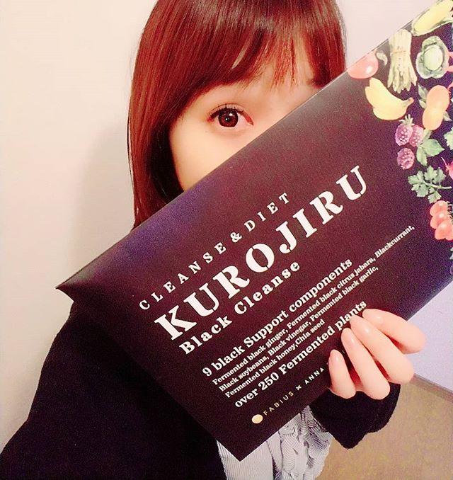 黒汁(KUROJIRU)のパッケージを持つ女性