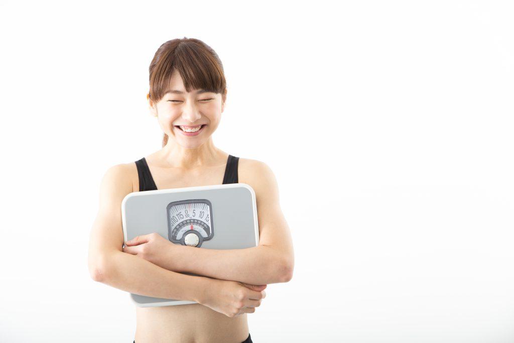 体重計を抱えて笑顔の女性