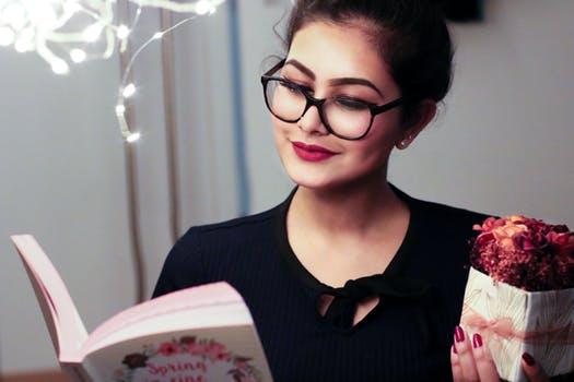 商品を持ちながら本を見て調べる女性