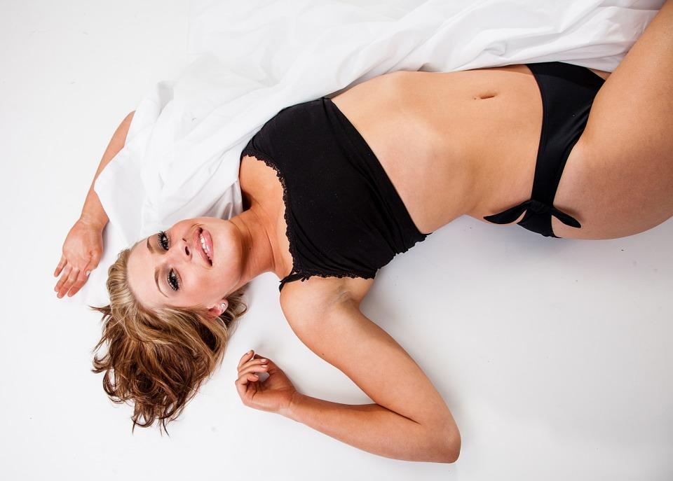 ベッドに横たわるスレンダーな女性