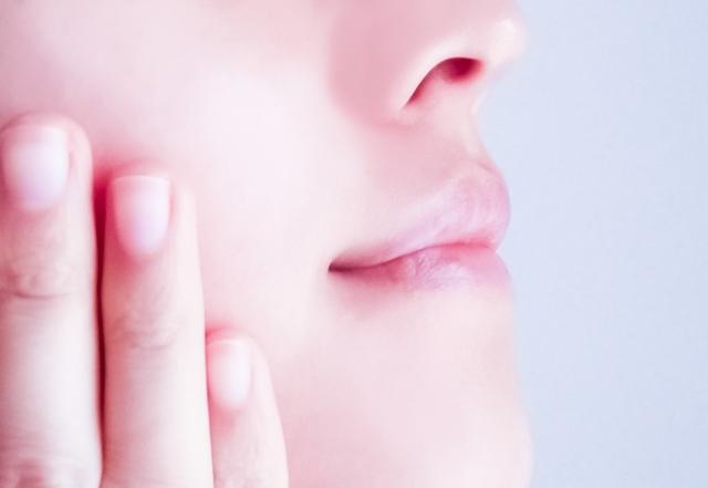 女性 肌 手を頬